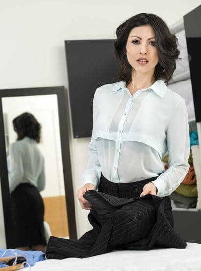 Lady in a corporate uniform stands next to mirror